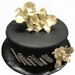 golden orchids on a black fondant birthday cake