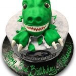 Fondant covered cake with fondant dinosaur head and jurassic park scan
