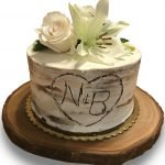 Carved birch stump buttercream cake with fresh flowers