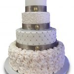 Four tier fondant covered wedding cake with ribbon and fondant broaches