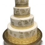 Fondant covered cake with gold paisley pattern and gold elephant topper