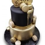 Two tiered black and gold fondant covered birthday cake with dripping gold chocolate and white and gold macarons