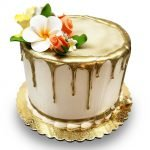 Assorted flowers and dripping gold chocolate birthday cake