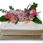 Fondant covered live floral birthday cake with gold ribbon