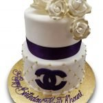Two tiered Chanel birthday cake with violet ribbon and logo