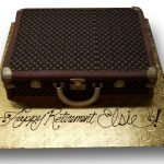 Fondant and scan covered Louis Vuitton suitcase cake with fondant handle and clasps