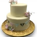 Pastel banner and gumpaste flowers baby shower cake