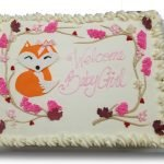 Fondant fox with buttercream leaves and branches on a whipped cream cake