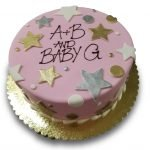 Gold and silver fondant stars and dots on a pink fondant covered cake