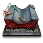 Skate ramp birthday cake with toy skateboards and drawn graffiti