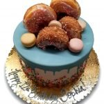 Donut and macaron cake with dripping blue chocolate and sprinkles