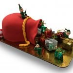Fondant covered santa's sack shaped cake with toy presents and elves