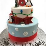 Fondant covered two tier birthday cake with fondant penguins and lights and sugar snowflakes