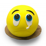 Fondant covered crying emoji cake